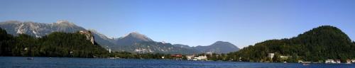Bled ze szmaragdowozielonym jeziorem, średniowiecznym zamkiem wzniesionym na skale i Alpami Julijskimi. #Słowenia #panorama